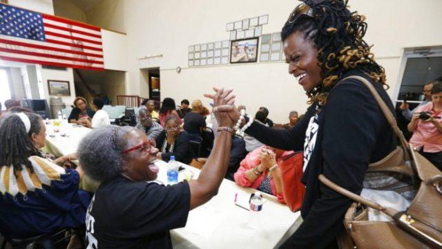 Black women grasping hands